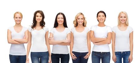 mujeres juntas: diseño de la ropa y la gente la unidad concepto - grupo de mujeres sonrientes felices en camisetas blancas y pantalones vaqueros en blanco