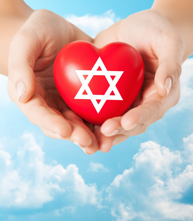 jewish community: religion, christianity, jewish community and charity concept - close up of female hands holding red heart with star of david symbol over blue sky and clouds background