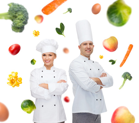 cooking, profession, vegetarian diet and people concept - happy chef couple or cooks with crossed hands over falling vegetables background