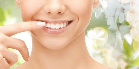 ortodoncia: salud dental, la belleza, la higiene y la gente concepto - cerca de la sonriente cara de la mujer que señala a los dientes sobre fondo verde natural
