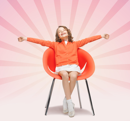 designer chair: people, happiness, childhood and furniture concept - happy little girl sitting on designer chair over pink burst rays background