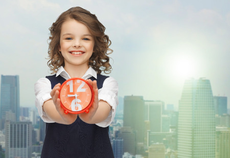 punctuality: people, childhood, time and punctuality concept - happy girl with alarm clock over city background Stock Photo