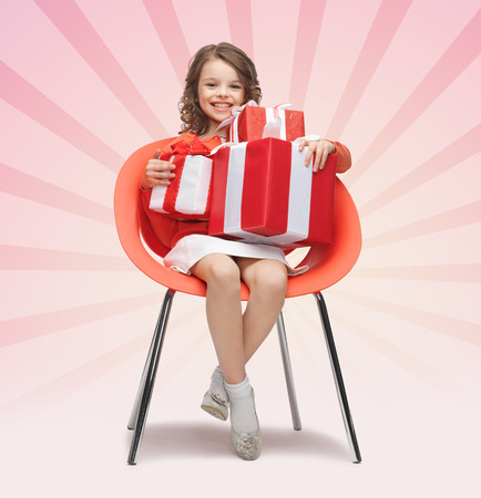 people sitting on chair: people, christmas, holidays, presents and childhood concept - happy little girl with gift boxes sitting on chair over pink burst rays background