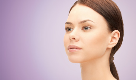 teen girl smile face: health, people and beauty concept - beautiful young woman face over violet background Stock Photo