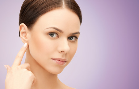 people, beauty, hearing and healthcare concept - face of beautiful woman touching her ear over violet background Фото со стока