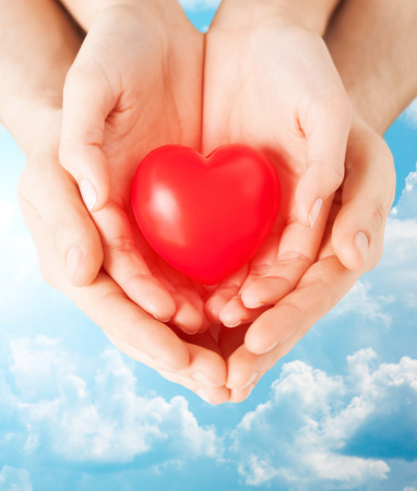 health, love and relationships concept - close up of couple hands with big red heart over blue sky and clouds background photo