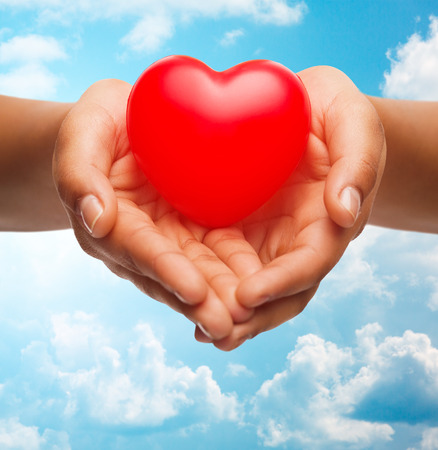 health, medicine, love, valentines day and charity concept - close up of african american female hands holding small red heart over blue sky and clouds background
