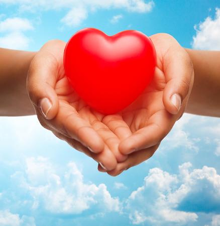 donacion de organos: la salud, la medicina, el amor, día de San Valentín y la caridad concepto - cerca de africano americano manos femeninas que sostienen el pequeño corazón rojo en el cielo azul y nubes de fondo