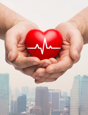 family health, charity and medicine concept - close up of hands holding red heart with cardiogram over city skyscrapers background photo
