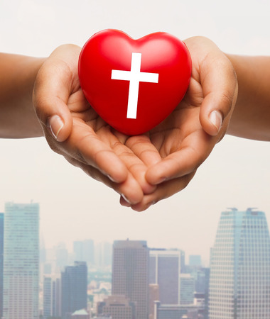 people  background: religion, christianity and charity concept - close up of female hands holding red heart with christian cross symbol over city skyscrapers background