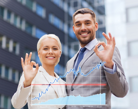 ok: business, partnership, gesture success and people concept - smiling businessman and businesswoman making ok gesture over office building background