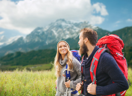 adventure, travel, tourism, hike and people concept - smiling couple walking with backpacks over alpine mountains background