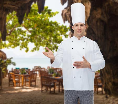 invitando: la cocina, la profesión y la gente concepto - feliz cocinero de sexo masculino cocinar invitando a más de salón restaurante en la playa