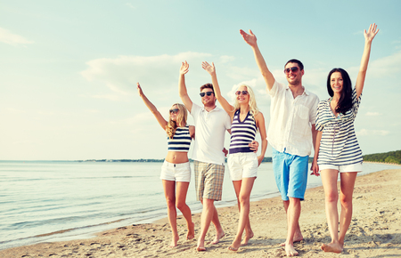 summer, holidays, sea, tourism and people concept - group of smiling friends in sunglasses walking on beach and waving hands photo