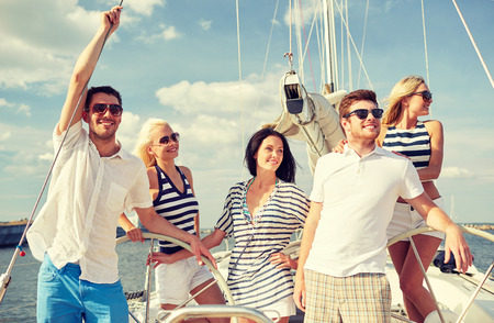 sailing ship: vacation, travel, sea, friendship and people concept - smiling friends sailing on yacht