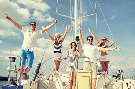 bateau voile: vacances, Voyage, mer, l'amitié et les concepts - sourire amis assis sur le pont de yacht et voeux