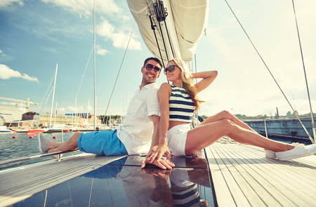 sailing ships: vacation, travel, sea, friendship and people concept - smiling couple sitting and talking on yacht deck