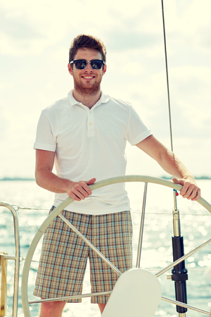 skipper: vacation, holidays, travel, sea and people concept - young man in sunglasses steering wheel on yacht