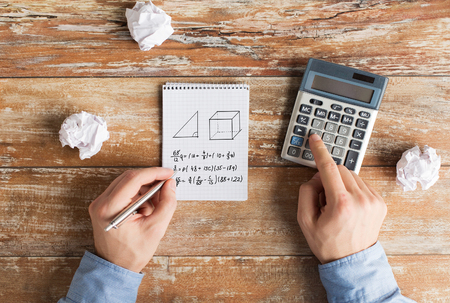 cramped: business, education, people and technology concept - close up of male hands with calculator, cramped paper wads and notebook solving geometric task Stock Photo