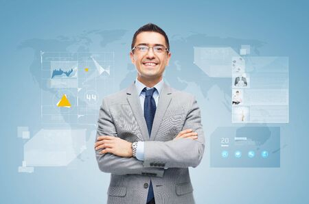 people development: business, people, development and technology concept - happy smiling businessman in suit working with virtual screens over blue background Stock Photo