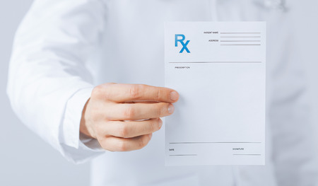 holding close: close up of male doctor holding rx paper in hand Stock Photo