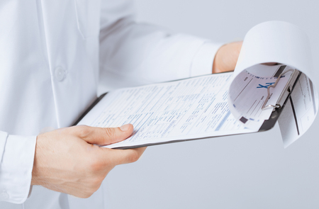 druggist: close up of male doctor holding prescription paper in hand