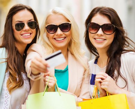 chicas comprando: compras y concepto de turismo - hermosas chicas con bolsas de la compra y la tarjeta de crédito en ctiy Foto de archivo