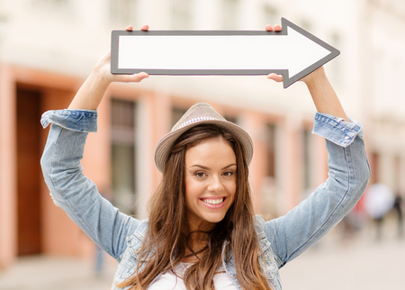 holidays and tourism concept - beautiful girl showing direction with arrow in the city photo
