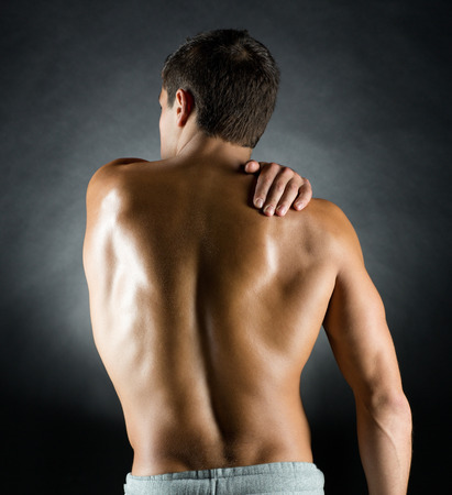 pain relief: pain relief, sport, bodybuilding, strength and people concept - young man standing over black background Stock Photo