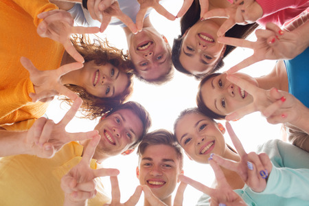 mates: friendship, youth, gesture and people - group of smiling teenagers in circle showing victory sign Stock Photo
