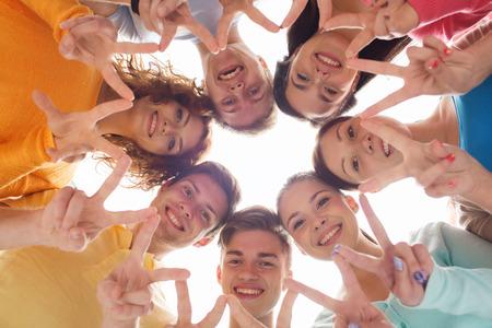 juventud: la amistad, la juventud, el gesto y la gente - grupo de adolescentes sonrientes en círculo que muestra signo de la victoria