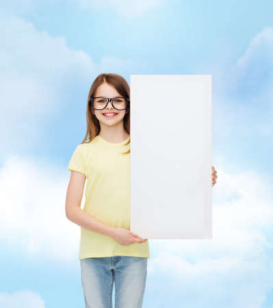 commercial medicine: vision, health, advertisement and people concept - smiling little girl wearing eyeglasses with white blank board