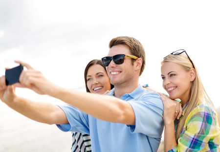 summer holidays, vacation, happy people concept - group of friends taking selfie with cell phone on the beach Imagens