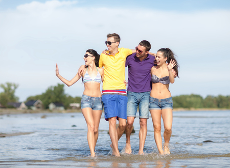 summer holidays, vacation, tourism, travel and people concept - group of happy friends walking and waving hands along beach photo