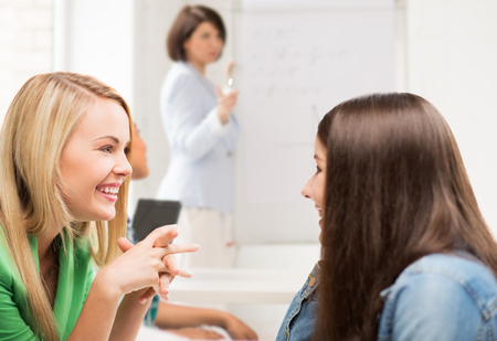gossiping: education concept - student girls gossiping at school Stock Photo
