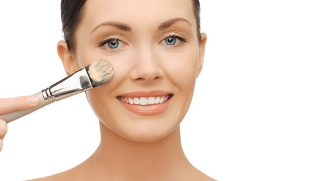 makeup applying: beauty and makeup concept - woman applying liquid foundation with brush