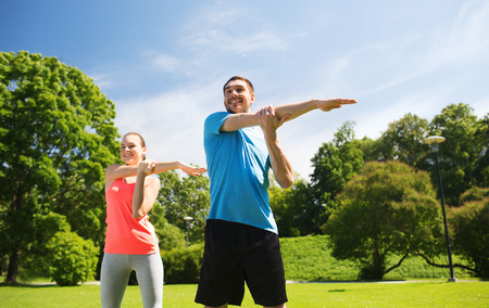 stretches: fitness, sport, training and lifestyle concept - smiling couple stretching outdoors