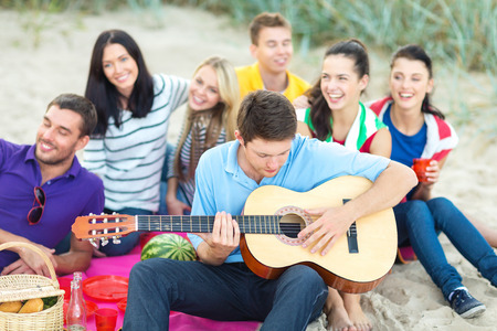 chill out: summer holidays, vacation, music, happy people concept - group of happy friends playing guitar on beach