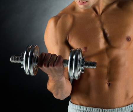 male torso: sport, bodybuilding, training and people concept - close up of young man with dumbbell flexing muscles over gray background