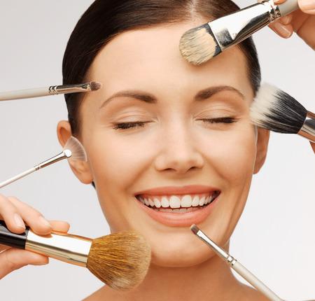 la belleza y el concepto de maquillaje - primer retrato de la hermosa mujer que consigue maquillaje profesional con muchos cepillos