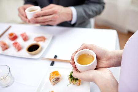 comida japonesa: restaurante, comida, gente, japonés y asiático concepto de cocina - cerca de la pareja beber té en el restaurante