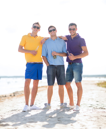 nonalcoholic beer: summer holidays, vacation, people and bachelor party concept - group of happy male friends drinking beer and walking along beach Stock Photo