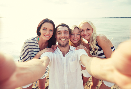 family portrait: summer, sea, tourism, technology and people concept - group of smiling friends with camera on beach photographing and taking selfie