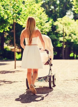 가족, 자녀와 부모 개념 - 행복의 어머니는 뒤에서 공원에서 유모차와 함께 산책