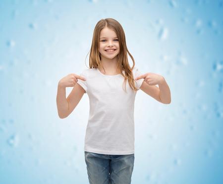 niño modelo: camiseta concepto de diseño - niña sonriente en blanco camiseta blanca apuntando a sí misma