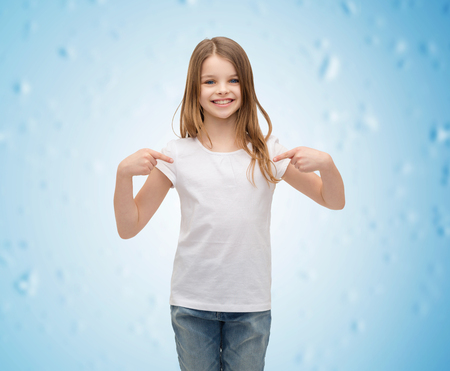 adorable child: t-shirt design concept - smiling little girl in blank white t-shirt pointing at herself