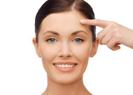 forehead: anti-aging concept - beautiful woman pointing to forehead Stock Photo