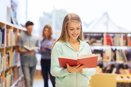 conocimientos: las personas, el conocimiento, la educaci�n y la escuela concepto - ni�a feliz estudiante o joven con el libro en la biblioteca