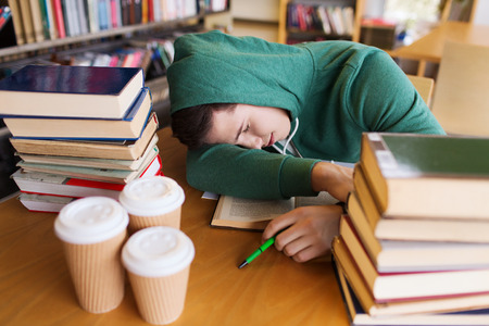 lazy: people, education, session, exams and school concept - tired student or young man with books and coffee sleeping in library