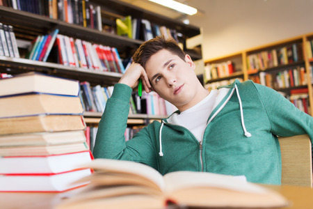 people, knowledge, education, literature and school concept - bored student or young man with books dreaming in library Stock Photo